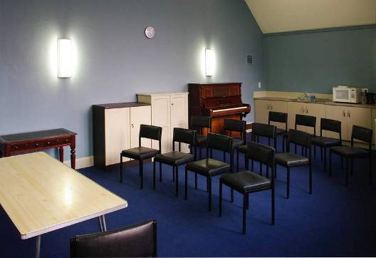 The Epworth room with tables, chairs, microwave and piano