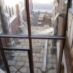 View from upstairs through the glass screen on to the paved area
