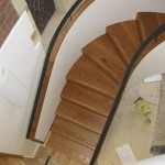 View down on to the bottom of the spiral staircase with handrails